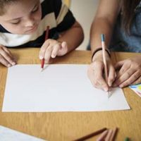 Sister and brother drawing at a table