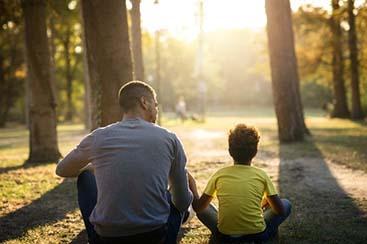 father-daughter-sitting-grass-park-enjoying-sunset-together_342744-975