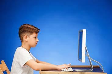 school-age-boy-sitting-front-monitor-laptop_155003-13706